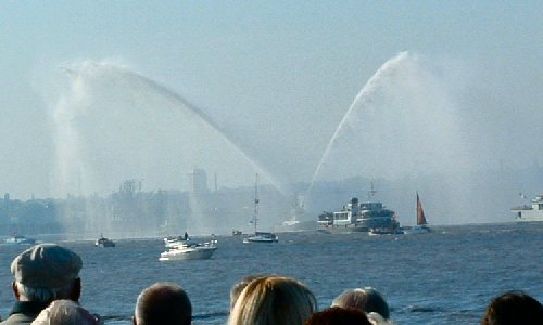 A fire fighting tug spraying water